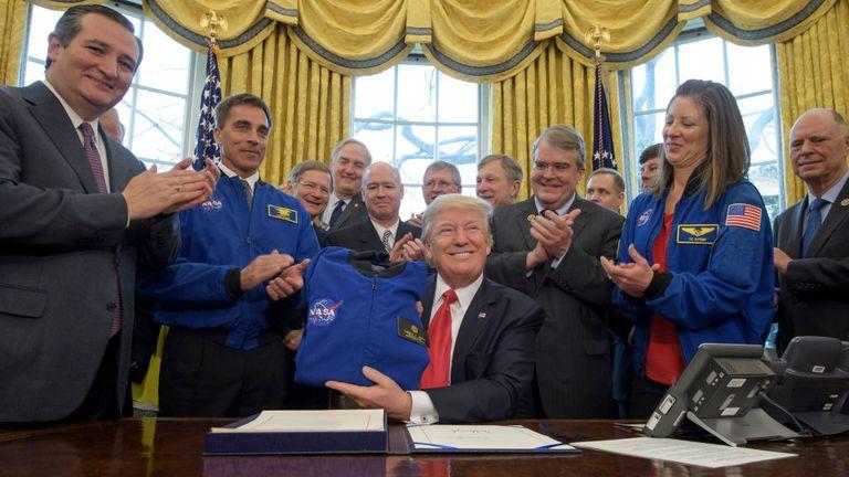 Le président Donald Trump, au centre, détient une veste de vol de la NASA qui lui est présentée par le chef du bureau des astronautes de la NASA Chris Cassidy, veste bleue à gauche, après avoir signé la NASA Transition Authorization Act of 2017, aux côtés de membres du Sénat, du Congrès et de la National Aeronautics and Space Administration dans le bureau ovale de la Maison Blanche à Washington, le mardi 21 mars 2017. Également sur la photo, le sénateur Ted Cruz, R-Texas, à gauche, le chef du bureau des astronautes de la NASA, Chris Cassidy, veste bleue à gauche, représentant du président du comité des sciences, Lamar Smith , R-Texas, représentant John Culberson, R-Texas, droit du président, astronaute de la NASA Tracy Caldwell Dyson, et autres. Crédit photo: (NASA / Bill Ingalls)