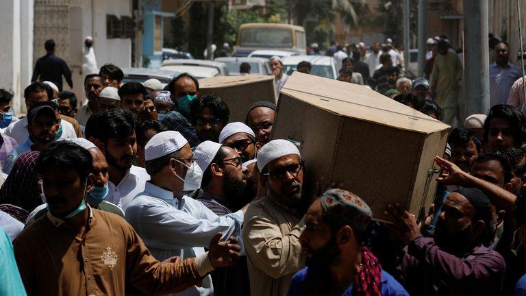 Des gens portent les cercueils de leur mari et de leur femme qui ont été tués dans un accident d'avion, lors d'un enterrement à Karachi