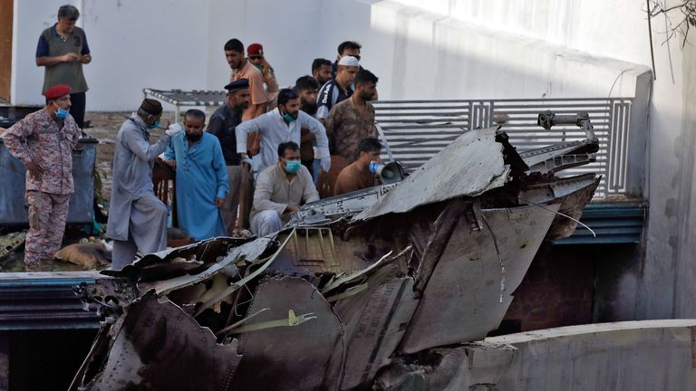 Des gens se tiennent à côté des débris d'un avion après s'être écrasé dans un quartier résidentiel près d'un aéroport à Karachi, au Pakistan, le 22 mai 2020. REUTERS / Akhtar Soomro