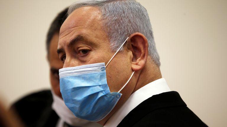 Le Premier ministre israélien Benjamin Netanyahu, portant un masque facial, regarde debout à l'intérieur de la salle d'audience alors que son procès pour corruption s'ouvre devant le tribunal de district de Jérusalem