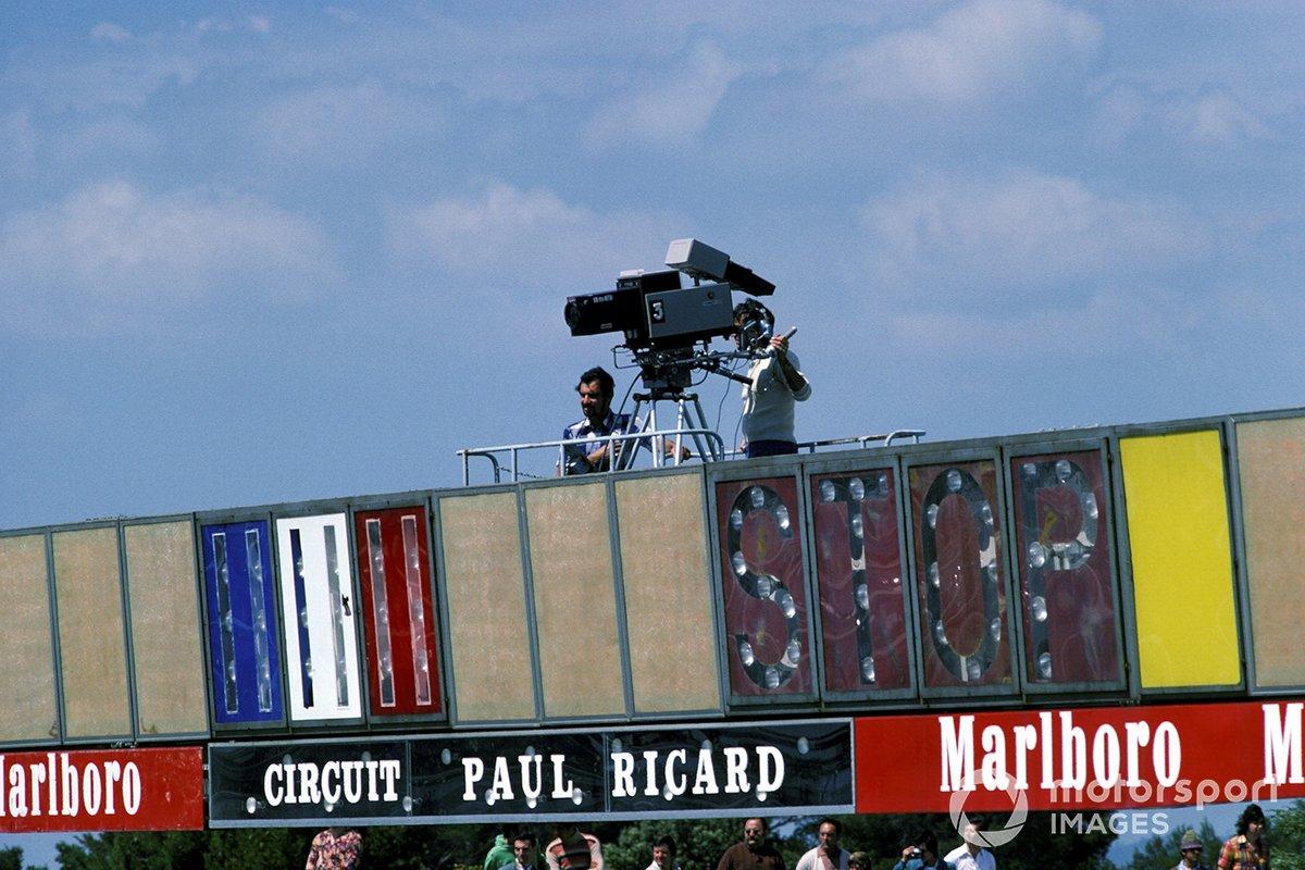 Un caméraman de télévision se prépare à filmer la course depuis le portique au-dessus de la ligne de départ / arrivée