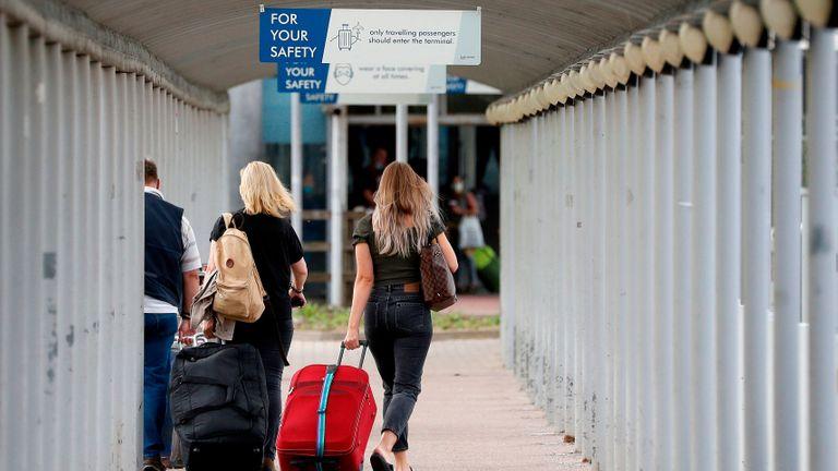 Les voyageurs tirent leurs valises à leur arrivée à l'aéroport de Londres Stansted, au nord-est de Londres, le 20 août 2020, suite à la décision de la compagnie aérienne britannique Easyjet de fermer ses opérations à l'aéroport à partir du 31 août (Photo par Adrian DENNIS / AFP) ( Photo par ADRIAN DENNIS / AFP via Getty Images)