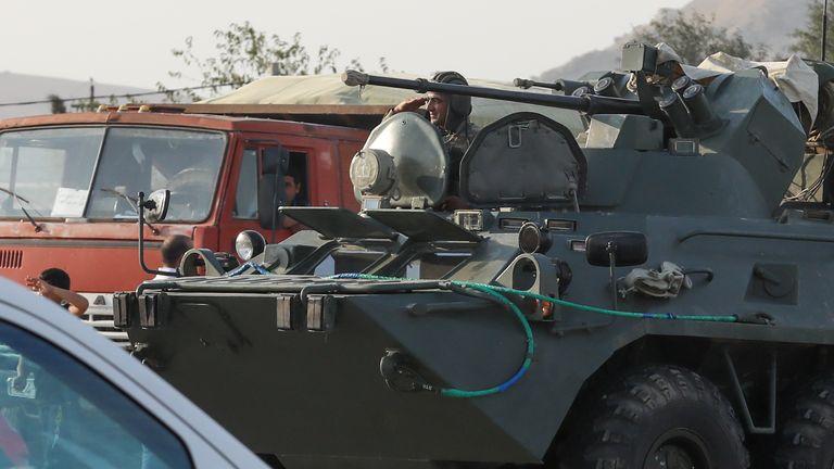Des gens accueillent dimanche des militaires azerbaïdjanais dans des véhicules militaires à Bakou