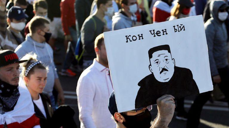 Un homme porte une pancarte représentant le président biélorusse en tant que dirigeant nord-coréen Kim Jong-un et lisant