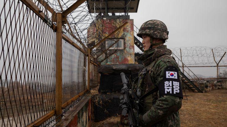 Sur une photo prise le 3 décembre 2018, un soldat sud-coréen se tient devant une clôture de sécurité à un poste de garde à l'intérieur de la zone démilitarisée (DMZ) près de la ligne de démarcation militaire (MDL) séparant la Corée du Nord et la Corée du Sud, dans le comté de Cheorwon en Corée du Sud.