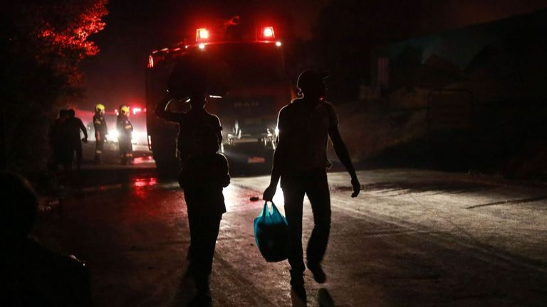 Des migrants partent alors qu'un feu brûle dans le camp de Moria sur l'île de Lesbos le 9 septembre 2020