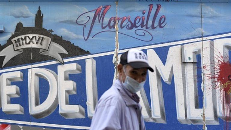 Un homme portant un masque facial marche devant un graffiti à Marseille
