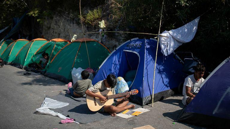 Un garçon joue de la guitare dans la zone où sont abrités les réfugiés et les migrants du camp détruit de Moria, près d'un nouveau camp temporaire, sur l'île de Lesbos, Grèce, le 16 septembre 2020. REUTERS / Alkis Konstantinidis