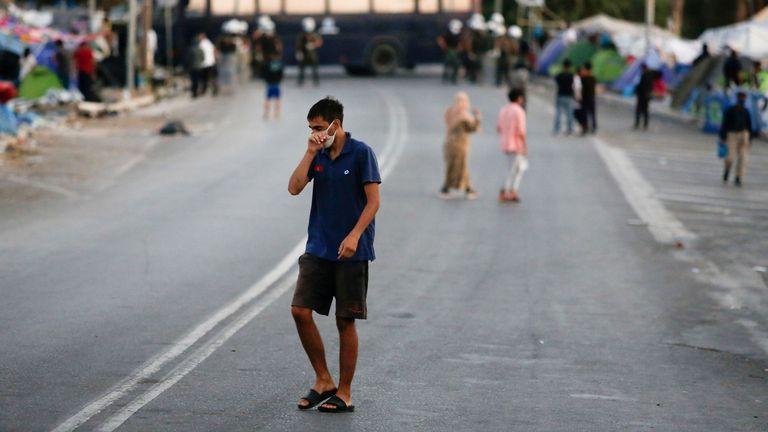 Un homme portant un masque protecteur fait son chemin le long d'une route bloquée par la police dans une zone où les réfugiés et les migrants du camp détruit de Moria sont abrités, lors d'une opération visant à les déplacer vers un nouveau camp temporaire, sur l'île de Lesbos, Grèce , 17 septembre 2020. REUTERS / Elias Marcou REFILE - CORRECTION DE LA DESCRIPTION DE L'OPERATION