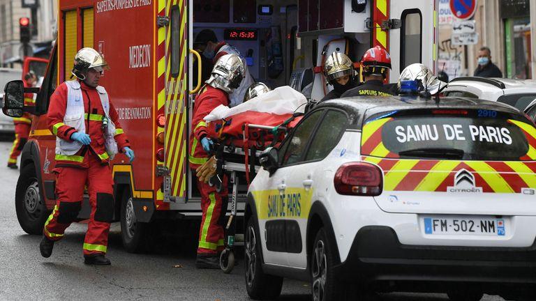 Les pompiers français chargent l'une des nombreuses personnes blessées dans une ambulance en attente près des anciens bureaux du magazine satirique français Charlie Hebdo à la suite d'une attaque présumée d'un homme brandissant un couteau dans la capitale Paris le 25 septembre 2020. - Les menaces coïncident avec le procès de 14 complices présumés des auteurs des massacres à Charlie Hebdo et dans un supermarché juif qui a fait au total 17 morts.  (Photo par Alain JOCARD / AFP) (Photo par ALAIN JOCARD / AFP via Getty Image