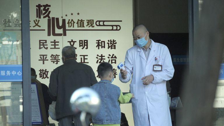 Des gens font vérifier leur température avant d'entrer dans un hôpital de Jiaxing, dans l'est de la Chine