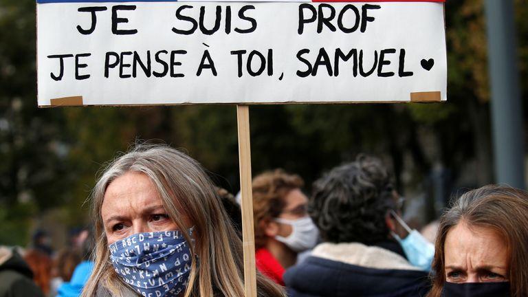 Une femme tient une banderole alors qu'elle assiste à un hommage à Samuel Paty, le professeur de français décapité dans les rues de la banlieue parisienne de Conflans St Honorine, place de la République, à Lille, France, le 18 octobre 2020. REUTERS / Pascal Rossignol