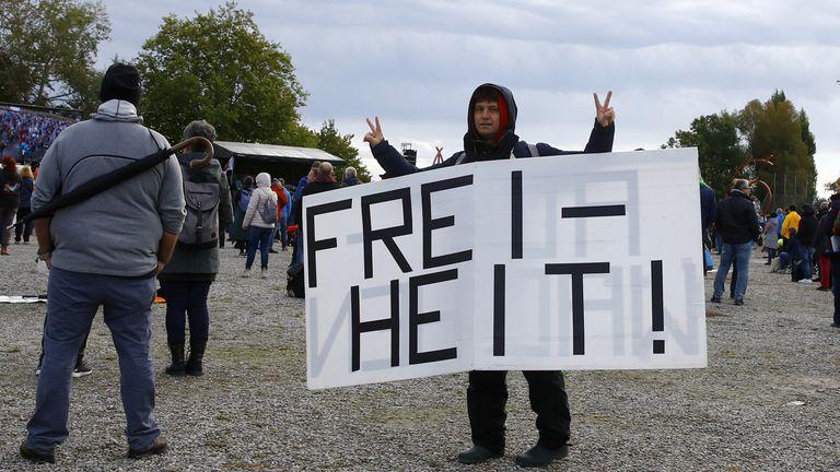 Un homme qui protestait contre les restrictions tenait une pancarte disant `` liberté ''