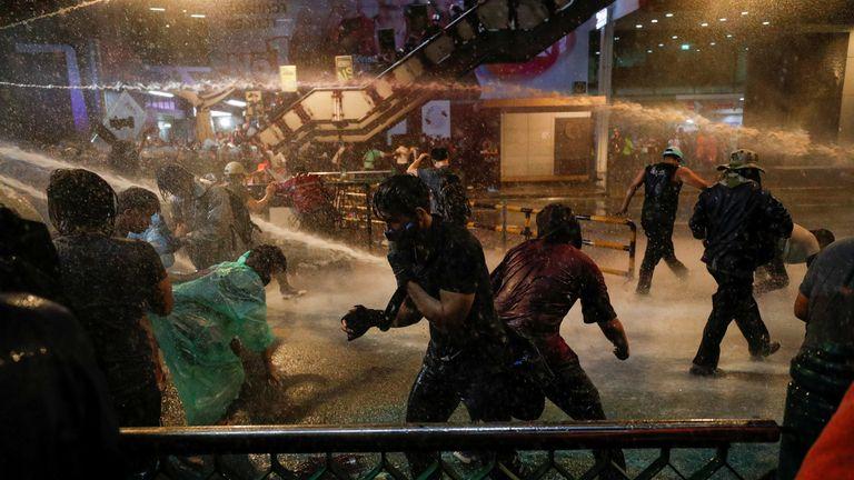 Des gens sont touchés par l'eau des canons à eau lors d'une manifestation anti-gouvernementale à Bangkok