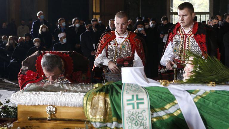 Un homme embrasse le cercueil du patriarche Irinej lors de la procession funéraire au Temple Saint Sava