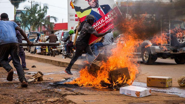 Un partisan de Bobi Wine portant une affiche de campagne pendant les manifestations