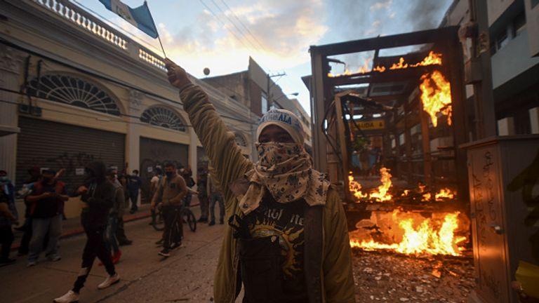 Un arrêt de bus brûle alors que les gens manifestaient samedi à Guatemala City
