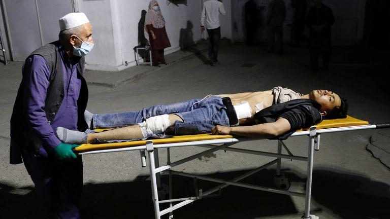 Un homme afghan roule un homme blessé dans un hôpital après un attentat suicide à Kaboul, Afghanistan, le 24 octobre 2020. REUTERS / Mohammad Ismail