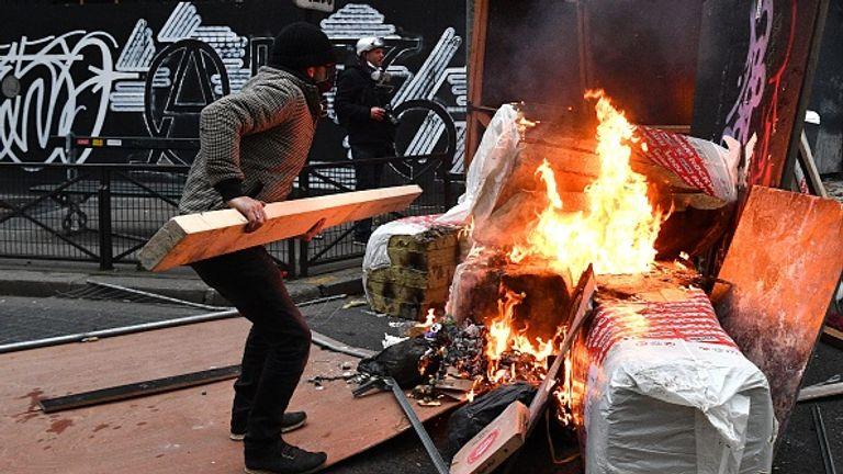 Un manifestant jette du bois sur une barricade lors de manifestations à Paris