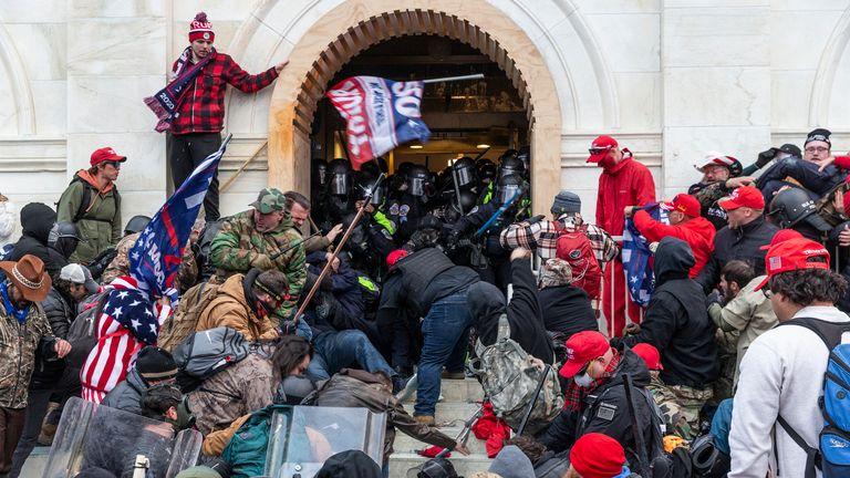 WASHINGTON DC, DISTRICT DE COLOMBIE, ÉTATS-UNIS - 2021/01/06: des émeutiers affrontent la police essayant d'entrer dans le bâtiment du Capitole par les portes d'entrée.  Les émeutiers ont brisé des fenêtres et ont violé le bâtiment du Capitole pour tenter de renverser les résultats des élections de 2020.  La police a utilisé des matraques et des grenades lacrymogènes pour finalement disperser la foule.  Les émeutiers ont également utilisé des barres de métal et des gaz lacrymogènes contre la police.  (Photo par Lev Radin / Pacific Press / LightRocket via Getty Images)