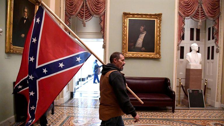 Un partisan de Donald Trump porte un drapeau de bataille confédéré dans le Capitole américain