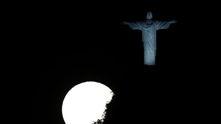 Une pleine lune illumine la statue du Christ Rédempteur à Rio de Janeiro, Brésil