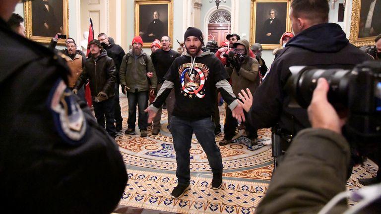 Un partisan du président Donald Trump affronte la police alors que les partisans de Trump manifestent au deuxième étage du Capitole américain près de l'entrée du Sénat après avoir enfreint les défenses de sécurité, à Washington, États-Unis, le 6 janvier 2021. REUTERS / Mike Theiler