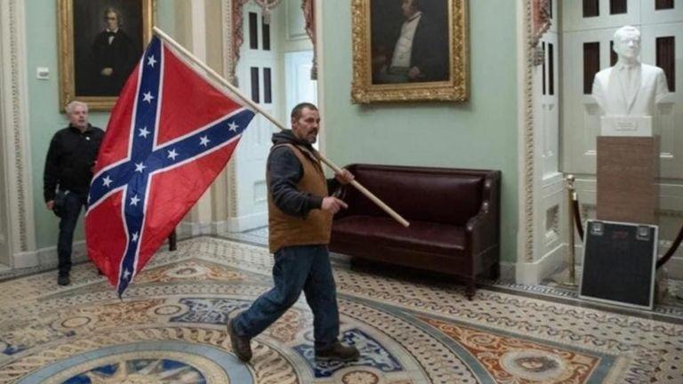 Cet homme a été vu portant un drapeau confédéré à l'entrée de la chambre du Sénat