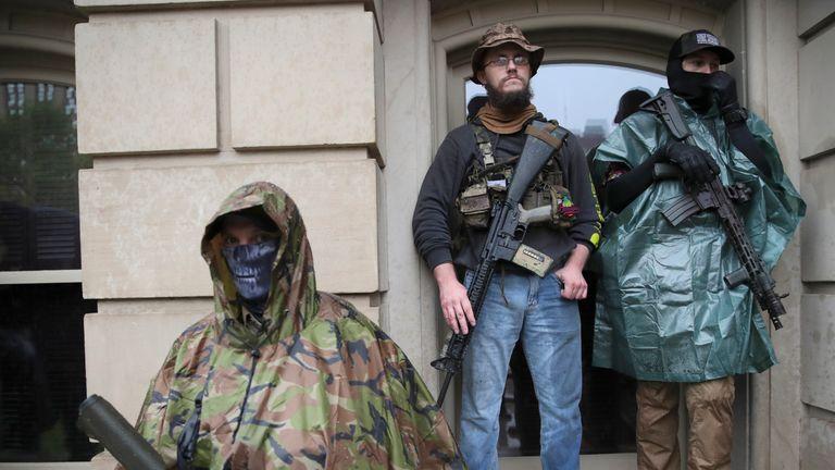 Les manifestants se tiennent avec leurs fusils lors d'un rassemblement au State Capitol à Lansing, Michigan, le jeudi 14 mai 2020 (AP Photo / Paul Sancya)