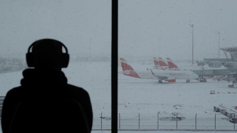 Une personne observe des avions stationnés à l'aéroport Adolfo Suarez Barajas, qui suspend ses vols en raison de fortes chutes de neige