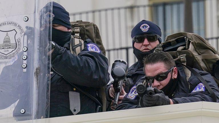 La police surveille les manifestants qui ont tenté de franchir une barrière policière, mercredi 6 janvier 2021, au Capitole à Washington.  Alors que le Congrès se prépare à affirmer la victoire du président élu Joe Biden, des milliers de personnes se sont rassemblées pour montrer leur soutien au président Donald Trump et à ses allégations de fraude électorale (AP Photo / John Minchillo)