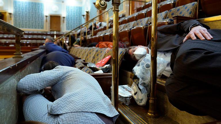 Les gens s'abritent dans la galerie de la Chambre alors que les manifestants tentent de pénétrer par effraction dans la salle de la Chambre du Capitole des États-Unis le mercredi 6 janvier 2021, à Washington.  (Photo AP / Andrew Harnik)