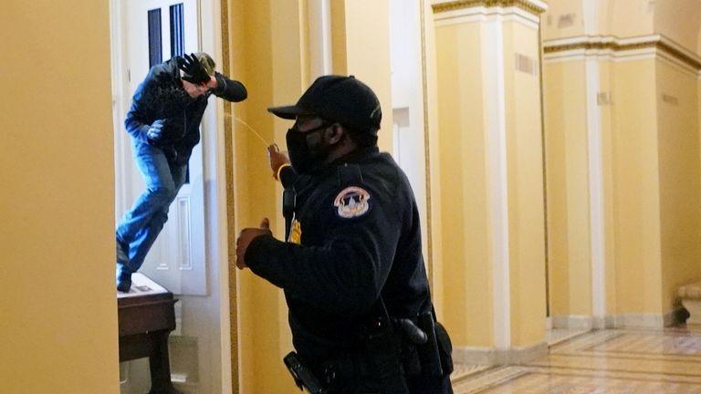 Un agent de police du Capitole américain tire du gaz poivré sur un manifestant qui tente d'entrer dans le bâtiment du Capitole lors d'une session conjointe du Congrès pour certifier les résultats des élections de 2020 au Capitole à Washington, États-Unis, le 6 janvier 2021. Kevin Dietsch / Pool via REUTERS TPX IMAGES DU JOUR