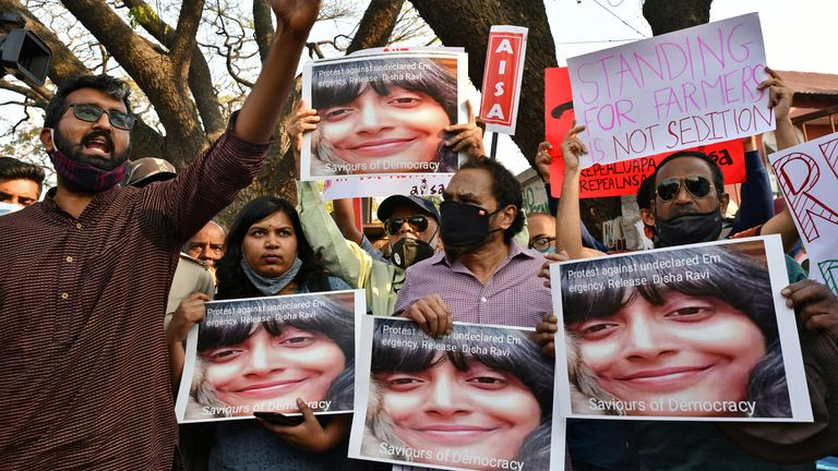 Des gens tiennent des pancartes et des photos de Disha Ravi lors d'une manifestation à Bengaluru